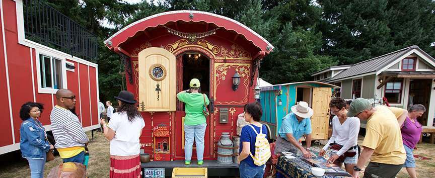image of people looking at tiny houses. The main focus is a gypsy wagon style tiny house with beautiful detailing