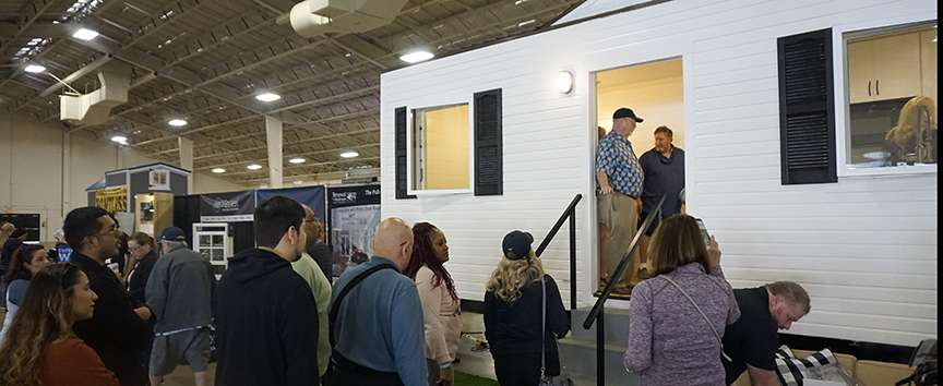 photo of several people waiting to tour a tiny house at an expo