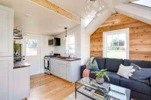 Interior of tiny house that house side extension. Mostly white with some wood. Clean look with a touch of warm wood.