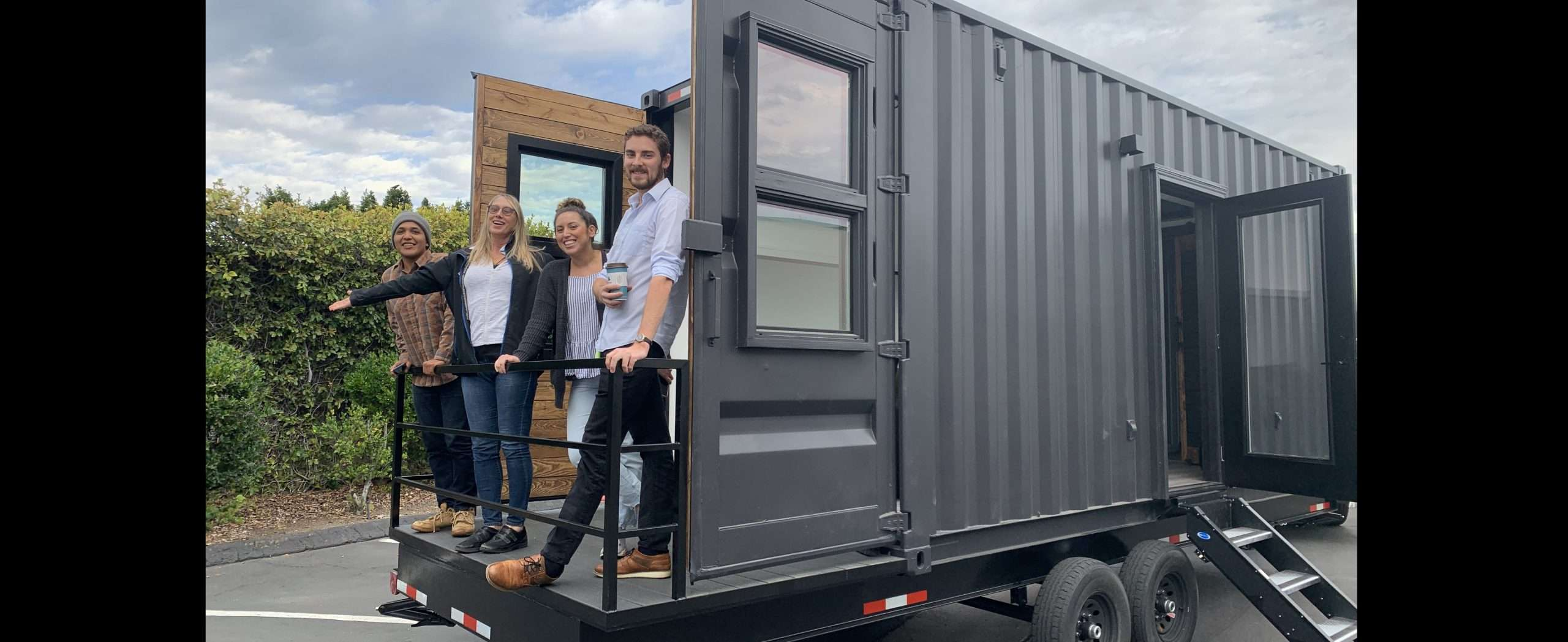 four people standing on the deck of a modern looking container home