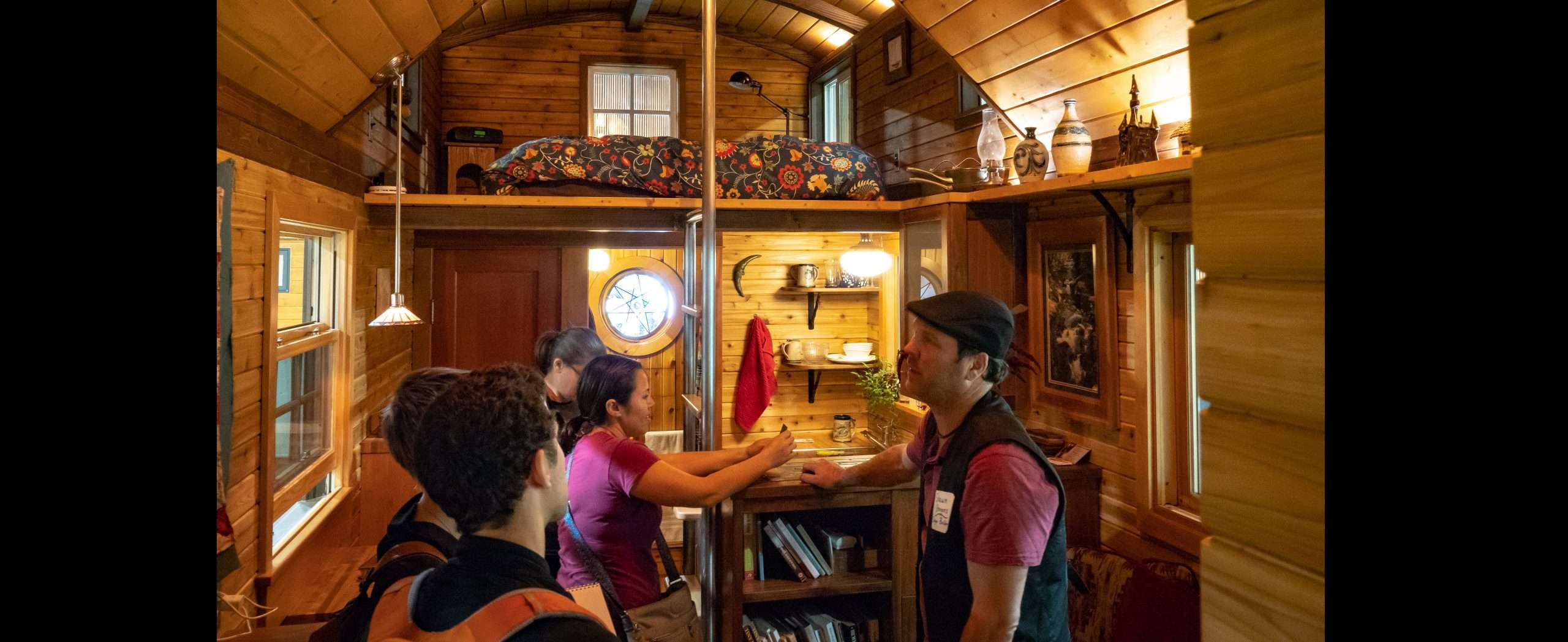 people talking inside of a tiny home. The interior has a lot of wood and it is very inviting and warm