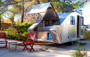 custom tear drop camper. Vintage spacey look. Back end is open with two red chairs sitting outside it.