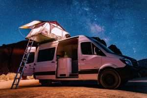 photo of an adventure van with a tent on top in ftont of a beautiful starry sky
