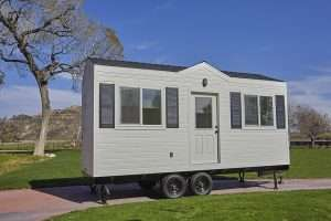 white tiny house on wheels with black shutters adn a door on the side