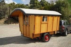 small vardo gypsy wagon pulled by an SUV