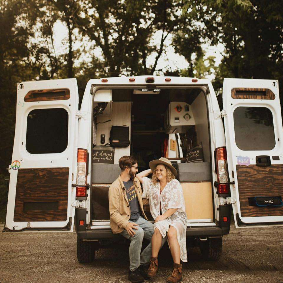 a couple sitting in the back of a camper van looking at each other lovingly