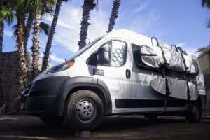 white campervan with two surfboards mounted on the side