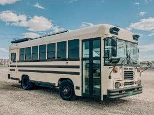 photo of a school bus turned into a camper. Painted cream./light tan and parked on on sand with blue sky above