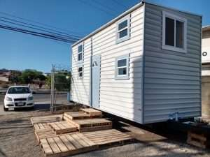 Tiny house on wheels with a deck that appears to be made from pallets