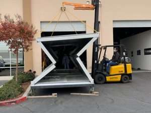 a metal box about the size of a shipping container being unfolded from flat pack to a box with a small crane the size of a forklift