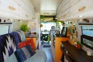 interior photo of a camper van with couch on the left and countertop on the right. Photo taken from the back toward the front (driving area)