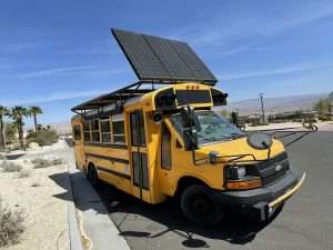 photo of a small school bus with a large solar panel on top tilted up