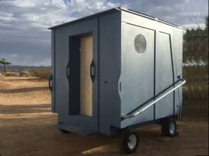 A very small box looking tiny house on four small wheels with a handle to move it manually on the outside