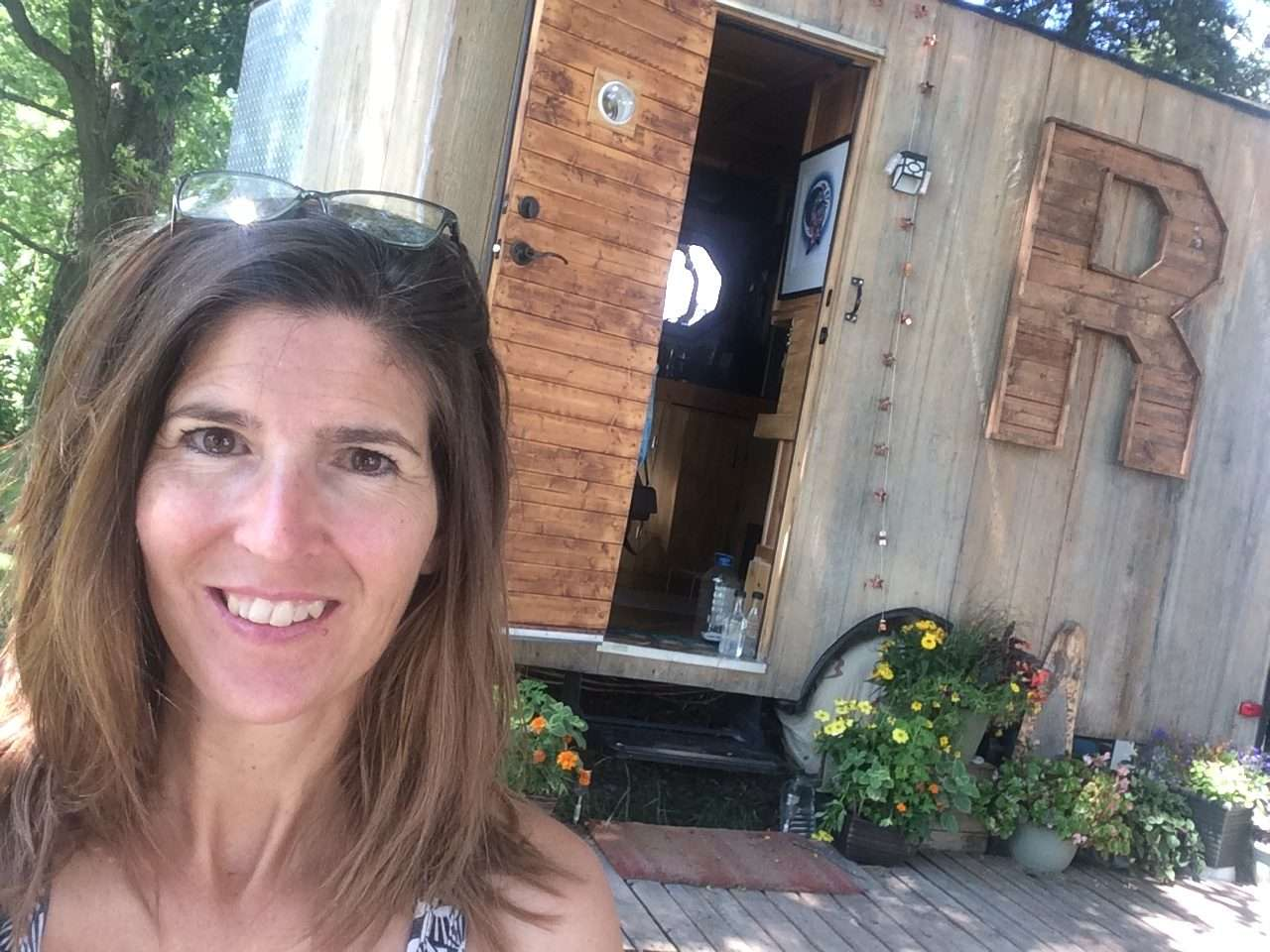 head and shoulder photo of a woman smiling standing in front of a tiny house on wheels with a big R on it