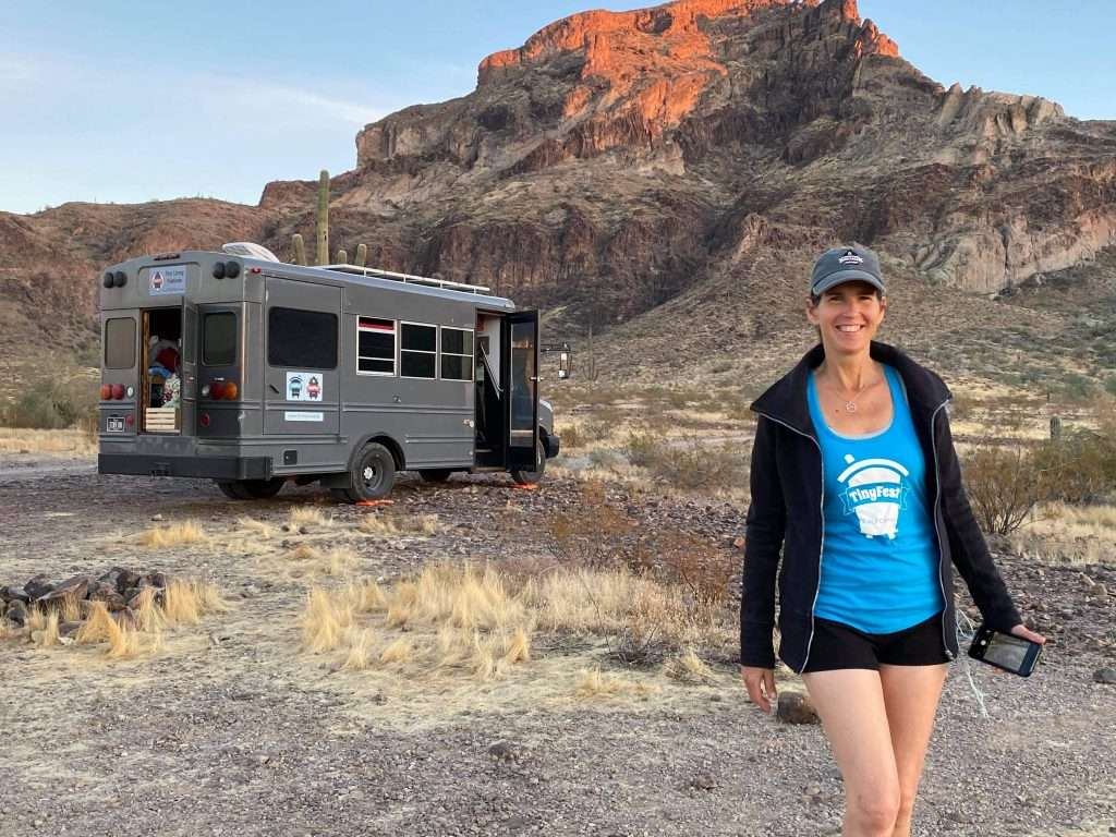 woman smiling as she walks away from a small gray bus parked in front of a a desert mountain