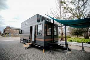 a tiny house on wheels that has striped siding and an awning set up in front of it