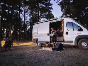 photo of a young man standing in front of the open doorway to his van playing electric guitar while in the woods
