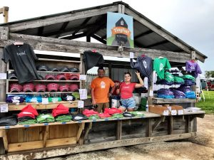 two people standing in the opening of an outdoor shirt shack