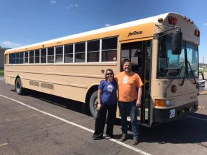 """A couple posing at the doorway of a school bus. They are wearing shirts that say """"TinyFest"""""""