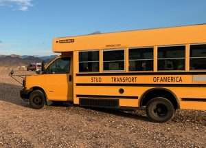 photo of a school bus with some of the letters missing on the side. It reads Stud Transport of America