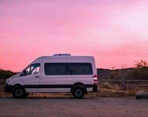 photo of a white camper van in front of a pink sky