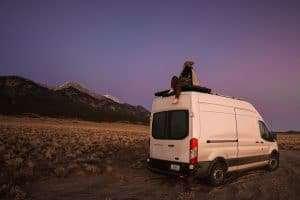 a young woman sitting on top of her white van as the sun sets and the sky turns a mix of dark blue & pink