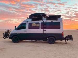 camper van ready loaded and for adventure parked on a beach with the sunset in the background