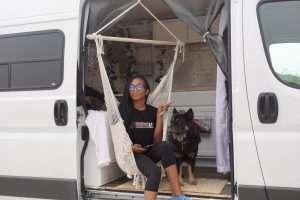 woman sitting in a macramé sling chair hanging in the doorway of her camper van