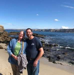 A couple in their 40s posing together in front of a rocky beach