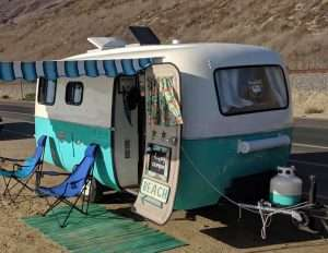 small vintage camper set up with an awning, rug, and two lawn chairs outside