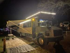 photo of a former school bus turned into a camper and parked in what looks like a campground with awning and rug out and picnic table. The photo was taken at night