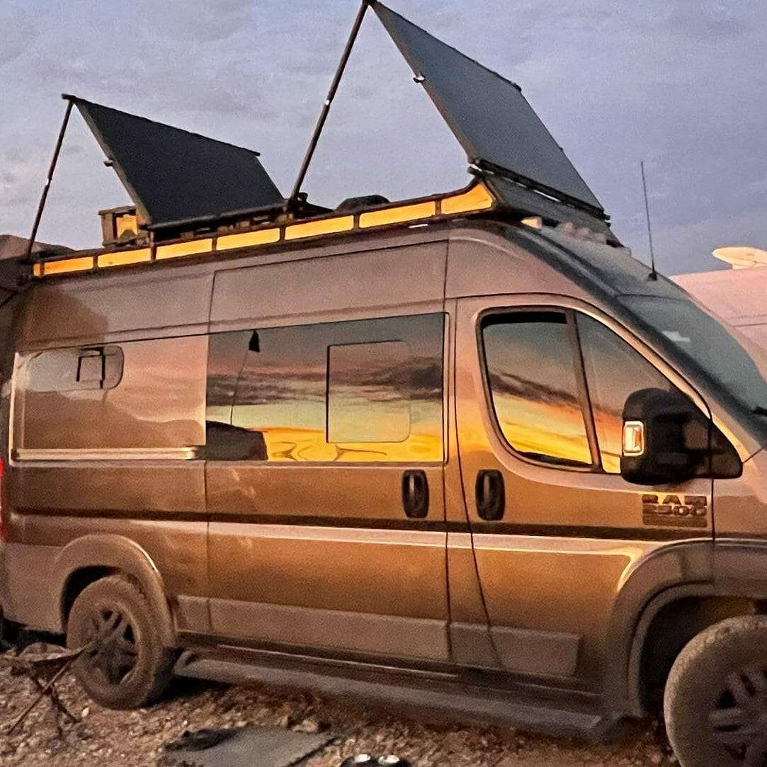 gray van with sunset reflecting on it bright yellow & orange. It has two solar panels on top standing up