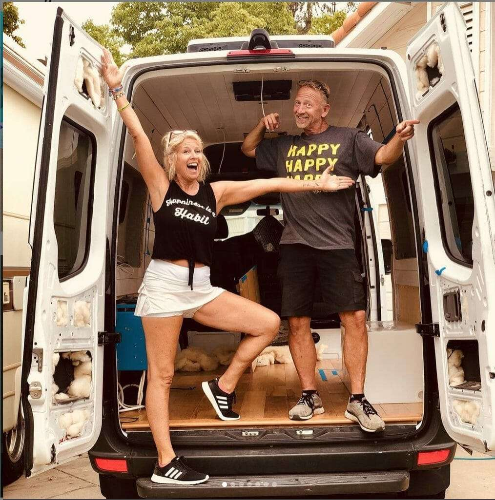an attractive couple in their 50s  standing in the back of their camper van looking very excited