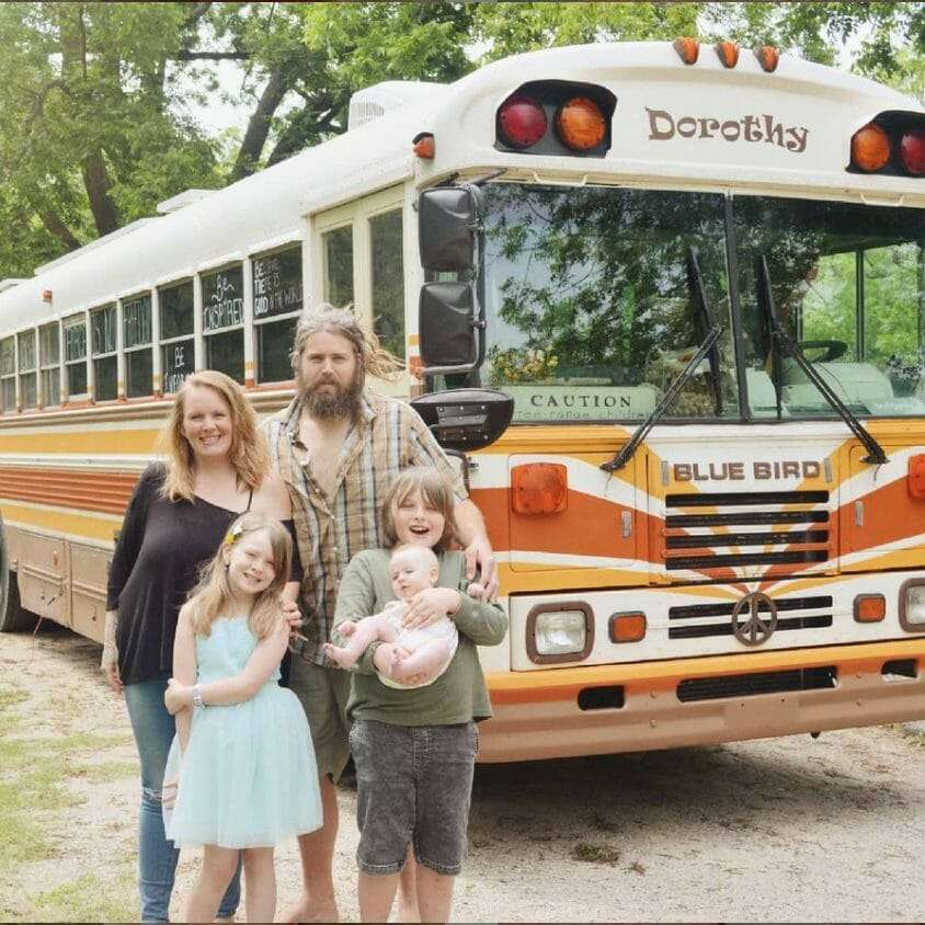 family of 5 standing in front of a school bus painted with retro style orange stripes and the name Dorothy on it.