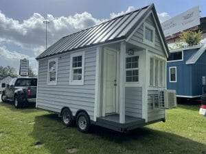 tiny house on wheels parked in the green grass