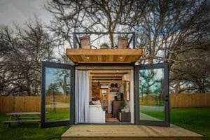 shipping container home  with big glass doors wide open and a rooftop deck