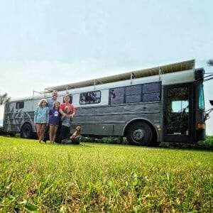 family standing front of a gray bus turned into an RV