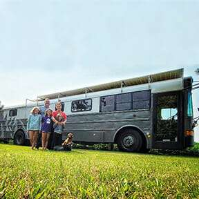 family staying in front of a bus turned into an RV