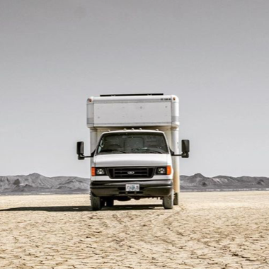 box truck parked on a flat desert sand area. no plant life in sight