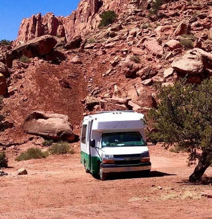 a shuttle bus on a red clay parking lot with red Rocky Mountains in the background